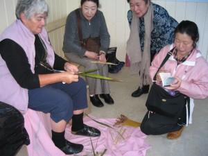 細長い葉で編みもの(weaving)を実演するトイさん。